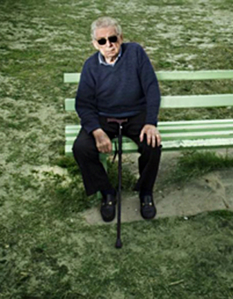 Man on a Bench with Dark Glasses and a Cane
